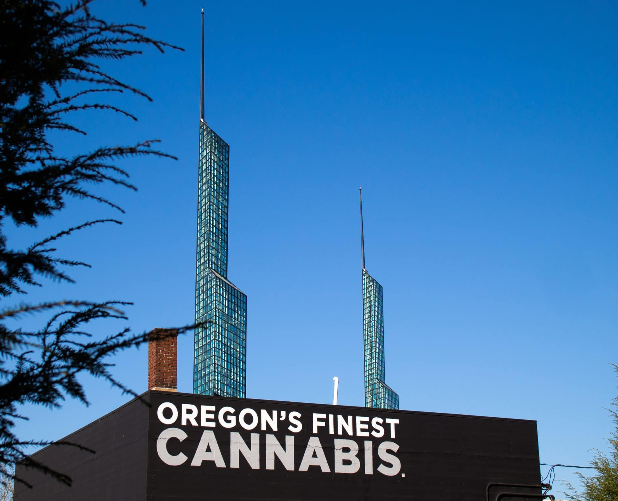 the top of the oregon's finest marijuana dispensary in front of the spires of the oregon convention center, with a bright blue sky as a backdrop