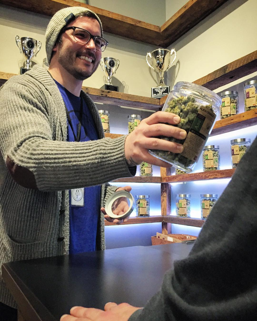 Oregon's Finest Customer Service; a staff member holds a jar of marijuana buds up for a customer to inspect