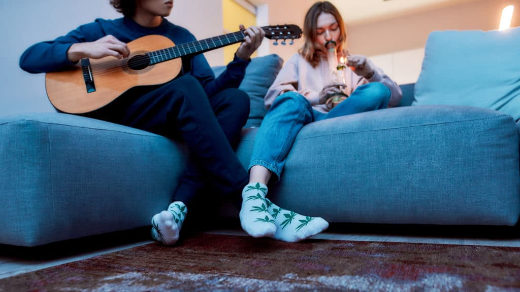 Young woman smoking marijuana from glass water pipe or bong, while her boyfriend or friend playing guitar. They relaxing on the sofa at home