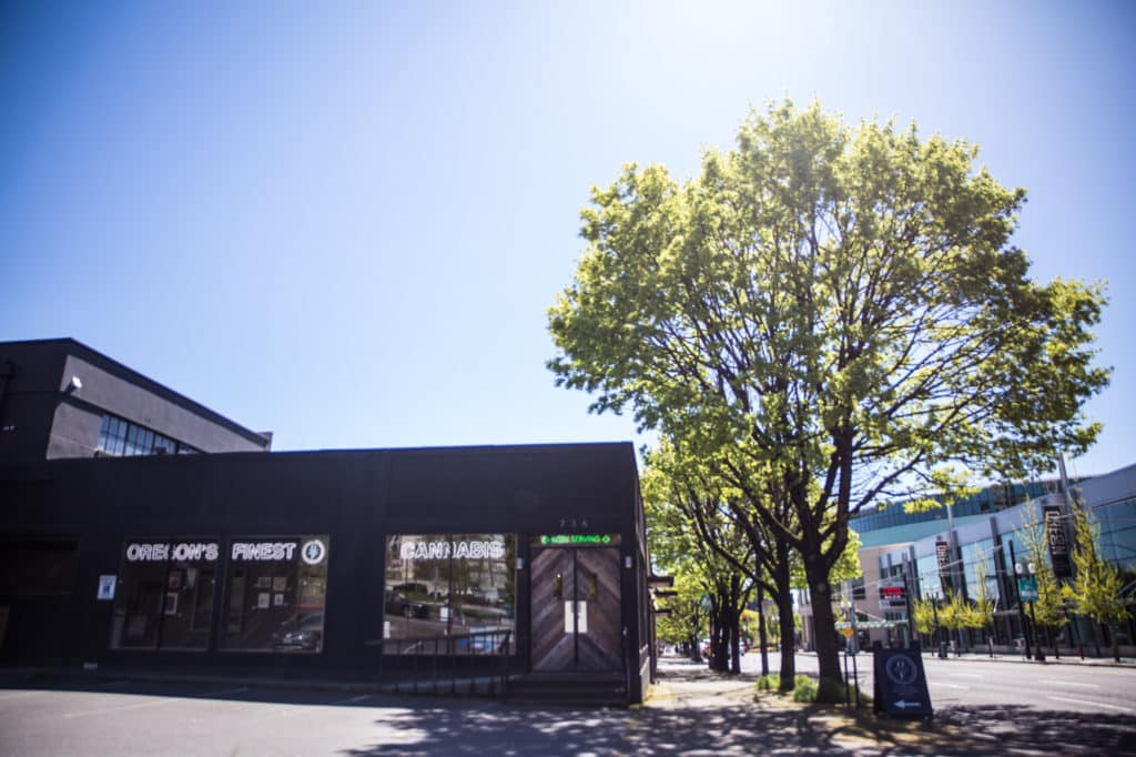 a black building housing the oregon's finest marijuana pickup and delivery dispensary, sunny skies shining through a large leafy tree