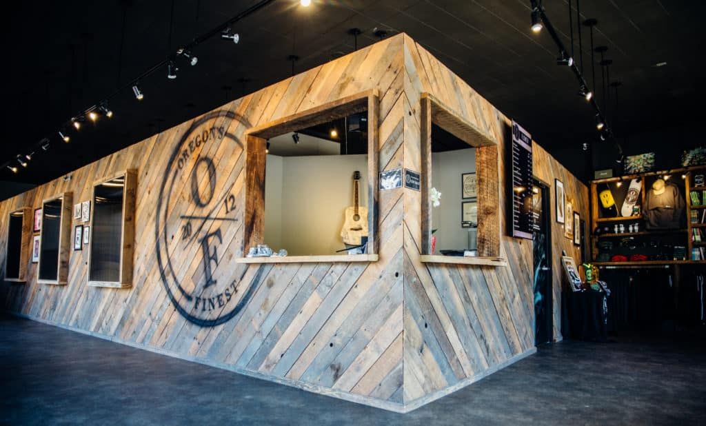 interior of the oregon's finest mlk location showing the barn wood walls branded with the oregon's finest logo